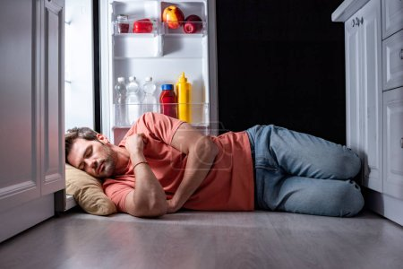 Photo for Exhausted man sleeping on floor in kitchen near open refrigerator - Royalty Free Image