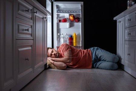 Photo pour Homme épuisé dormant près du réfrigérateur ouvert sur le plancher de cuisine - image libre de droit