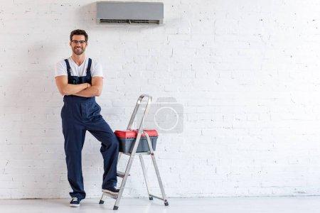 Photo pour Réparateur souriant debout sous climatiseur près escabeau et boîte à outils et en regardant la caméra - image libre de droit