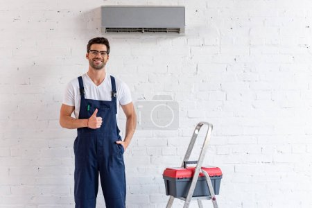 Foto de Cheerful repairman showing thumb up while standing under air conditioner near stepladder and toolbox - Imagen libre de derechos