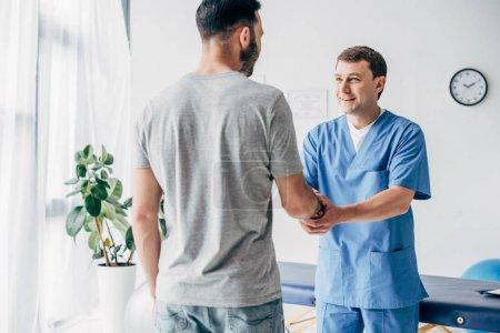 Photo pour Vue arrière du patient se serrant la main avec le docteur dans l'armoire de massage à la clinique - image libre de droit