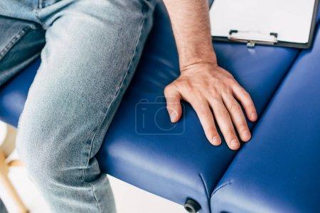 Photo pour Vue recadrée de l'homme assis sur le canapé dans l'armoire médicale - image libre de droit