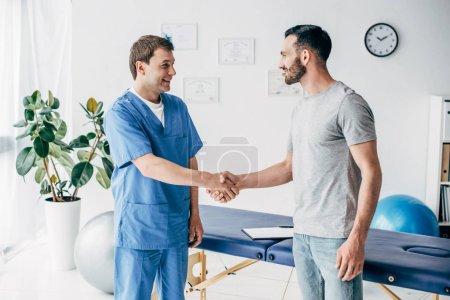 Photo pour Patient et docteur de sourire se serrant des mains près du divan dans le coffret de massage à la clinique - image libre de droit