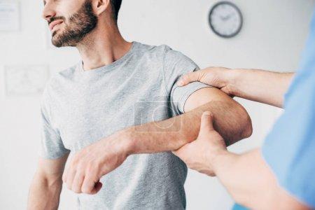 Photo pour Concentration sélective du patient souffrant de la douleur et du docteur examinant le bras patient dans l'armoire de massage à la clinique - image libre de droit