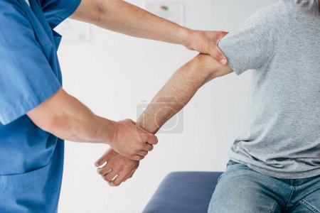 Photo for Cropped view of chiropractor manipulating with patient arm in massage cabinet at clinic - Royalty Free Image