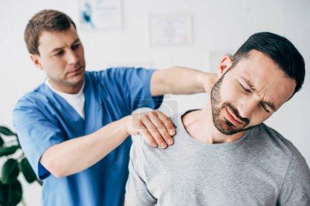 Photo pour Concentration sélective de l'homme souffrant et du médecin massant le cou de l'homme dans l'armoire de massage à la clinique - image libre de droit