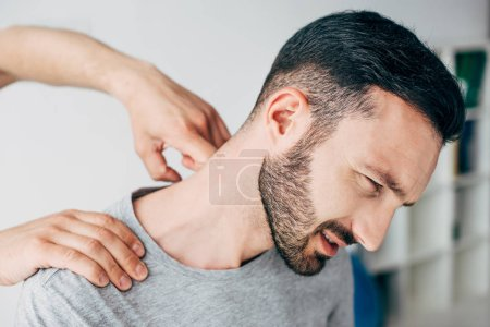 Photo for Chiropractor massaging neck of bearded man in hospital - Royalty Free Image