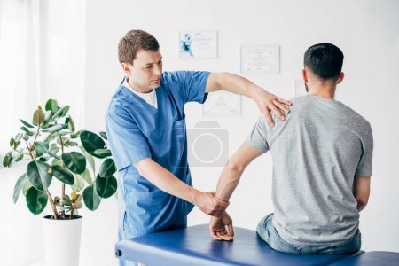 Photo pour Bras de massage de physiothérapeute du patient sur la table de massage à l'hôpital - image libre de droit