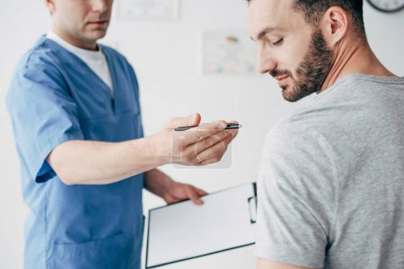 Photo for Physiotherapist with diagnosis and pen gesturing near patient in hospital - Royalty Free Image