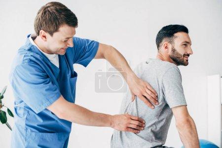 Photo pour Chiropraticien massant le dos de l'homme beau à l'hôpital - image libre de droit