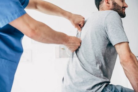 Photo for Physiotherapist massaging back of bearded man in hospital - Royalty Free Image