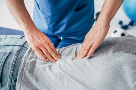 Photo for Cropped view of chiropractor massaging back of man in hospital - Royalty Free Image