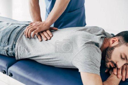 Photo pour Chiropractor massant le dos de l'homme sur la table de massage à l'hôpital - image libre de droit