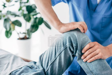 Photo for Cropped view of Physiotherapist massaging leg of patient in hospital - Royalty Free Image