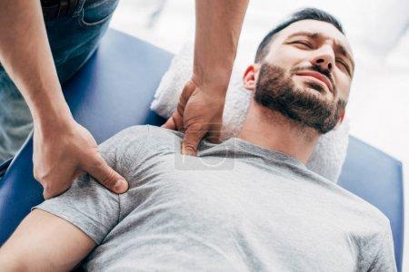 Photo pour Chiropractor massant l'épaule de l'homme se trouvant sur la table de massage à l'hôpital - image libre de droit