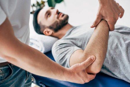 Photo pour Mise au point sélective de chiropraticien massage bras du patient à l'hôpital - image libre de droit