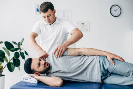 Photo pour Chiropraticien massant le bras du patient sur la table de massage à l'hôpital - image libre de droit