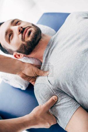 Photo pour Chiropractor massant l'épaule de l'homme beau sur la table de massage à l'hôpital - image libre de droit