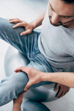 Photo pour Vue supérieure de la jambe de massage de physiothérapeute du patient s'asseyant sur la bille de forme physique à l'hôpital - image libre de droit