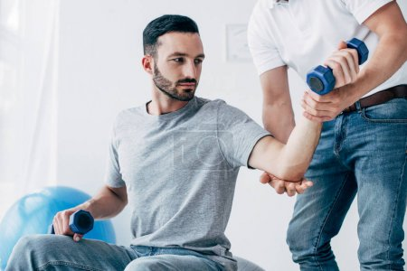 Photo for Chiropractor massaging arm of patient holding dumbbells in hospital - Royalty Free Image