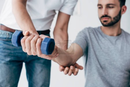 Photo for Chiropractor stretching arm of patient with dumbbell on grey - Royalty Free Image