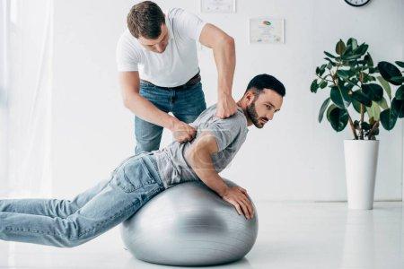 Photo pour Chiropractor massant le dos de l'homme se trouvant sur la bille de forme physique à l'hôpital - image libre de droit