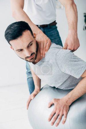 Photo pour Chiropractor massant le cou de l'homme se trouvant sur la bille de forme physique - image libre de droit