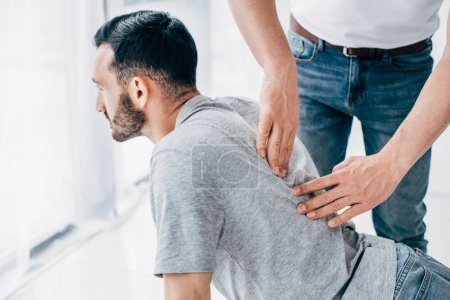 Photo for Chiropractor massaging back of bearded man in hospital - Royalty Free Image