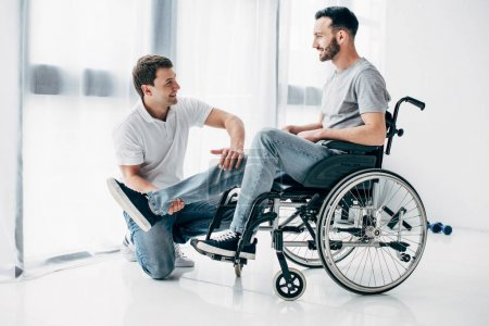 Photo for Smiling Physiotherapist massaging leg of handicapped man in wheelchair - Royalty Free Image
