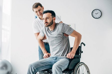 Photo for Physiotherapist helping handicapped man in Wheelchair during recovery in hospital - Royalty Free Image