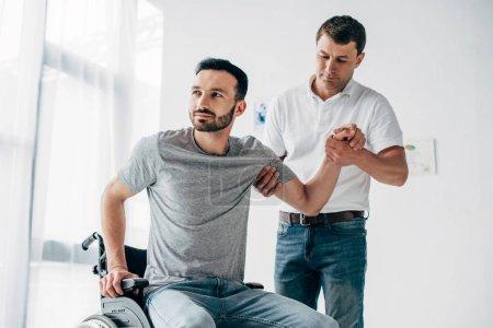 Photo pour Physiothérapeute aidant l'homme handicapé dans le fauteuil roulant pendant la récupération - image libre de droit
