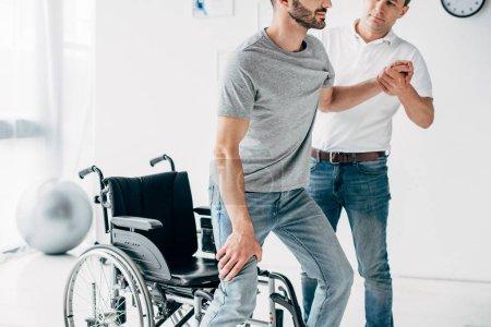 Photo pour Vue recadrée du physiothérapeute aidant l'homme handicapé pendant la récupération - image libre de droit
