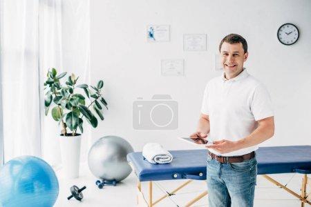 Photo pour Chiropraticien de sourire retenant la tablette numérique à l'hôpital et regardant l'appareil-photo - image libre de droit