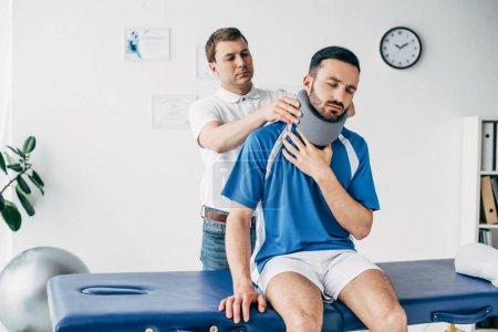 Photo pour Chiropraticien examinant le joueur de football dans l'accolade de cou à l'hôpital - image libre de droit