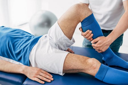 Photo for Cropped view of Physiotherapist massaging leg of football player in hospital - Royalty Free Image
