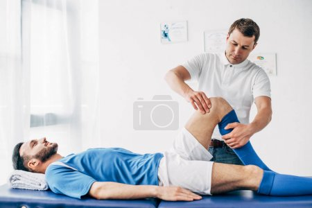 Photo for Handsome Physiotherapist massaging leg of football player in hospital - Royalty Free Image