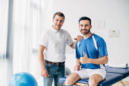 Photo pour Physiothérapeute de sourire près du joueur heureux de football affichant le pouce vers le haut à l'hôpital - image libre de droit