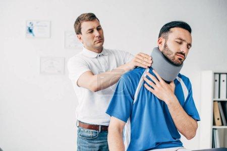 Photo pour Physiothérapeute examinant l'homme dans l'accolade de cou et l'uniforme de football pendant la récupération - image libre de droit