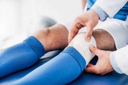Photo pour Vue partielle du physiothérapeute mettant le bandage élastique sur la jambe du joueur de football - image libre de droit