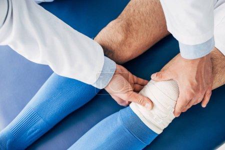 Photo pour Vue recadrée du physiothérapeute mettant un bandage élastique sur la jambe du joueur de football sur la table de massage - image libre de droit