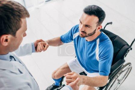 Photo pour Physiothérapeute aidant le joueur handicapé de football dans le fauteuil roulant pendant la récupération - image libre de droit