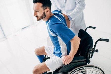 Photo for Physiotherapist helping handicapped football player in Wheelchair during recovery in hospital - Royalty Free Image