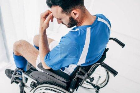 Photo pour Homme bouleversé dans l'uniforme de football se reposant dans le fauteuil roulant à l'hôpital - image libre de droit