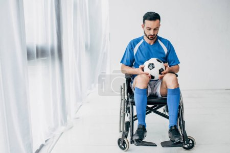 Photo for Man in football uniform sitting in Wheelchair and holding soccer ball - Royalty Free Image