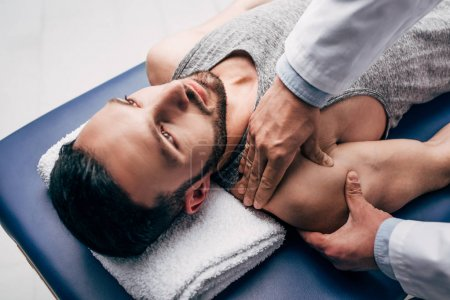 Photo for Chiropractor massaging shoulder of man on Massage Table in hospital - Royalty Free Image