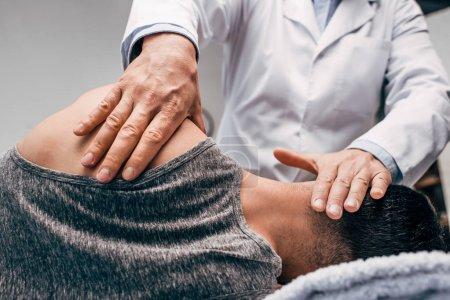Photo for Chiropractor in white coat massaging neck of man - Royalty Free Image
