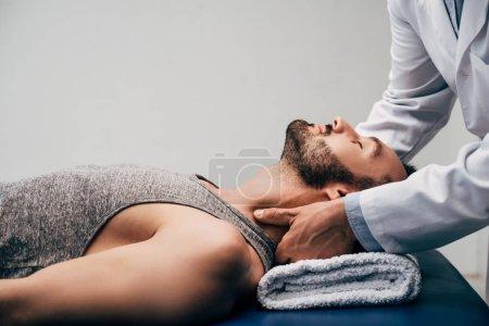 Photo pour Chiropractor massant le cou de l'homme beau se trouvant sur la table de massage sur le gris - image libre de droit