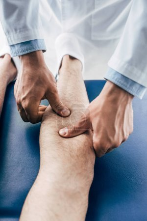 Photo for Partial view of Physiotherapist massaging leg of man in hospital - Royalty Free Image