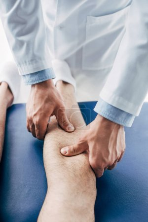 Photo for Crpped view of Physiotherapist massaging leg of man in hospital - Royalty Free Image
