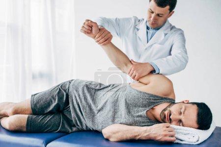 Photo pour Chiropraticien étirant le bras d'un beau patient allongé sur une table de massage à l'hôpital - image libre de droit